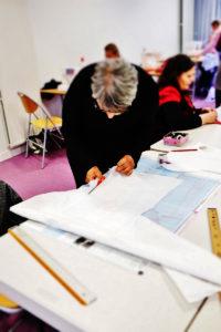 Une bénévole découpe un patron sur une table au Centre Social de Villejean